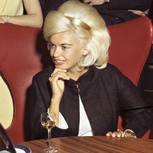 Jayne Mansfield istuu pöydän äärellä Suomen-vierailullaan tammikuussa 1964.