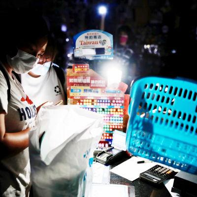 Henkilökunta valaisee taskulampulla kauppaa.