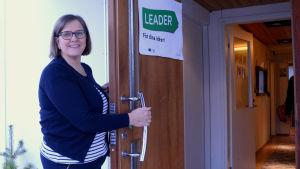 En kvinna ler mot kameran och håller upp en dörr.