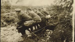 Soldater som sitter på en fälttoalett under första världskriget.