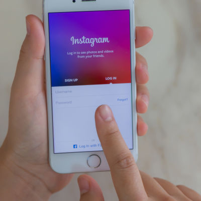 En hand och en telefon med Instagram uppe.