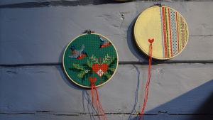 Två runda tavlor gjorda av återvunna julbroderier.