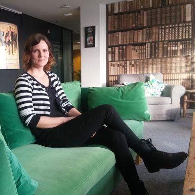 Terhi Alanko istuu vihreällä sohvalla.