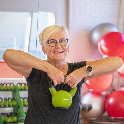 Lily Törmälä ja Henna Miinin nostelevat vihreitä kahvakuulia liikuntasalissa.