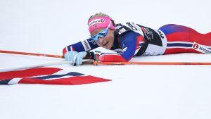 Therese Johaug ligger på snön med Norges flagga.