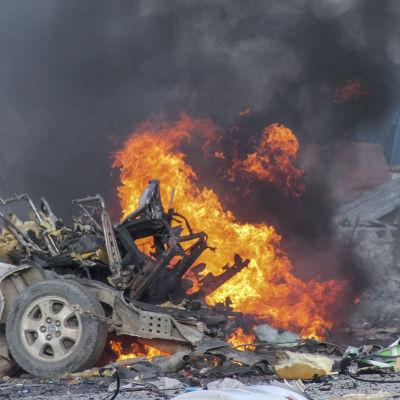 En bil brinner efter en explosion utanför hotell i Mogadishu.