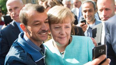 Angela Merkel tar en selfie med en flykting