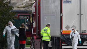 Polis står vid en lastbil. En del är klädda i skyddsutrustning.