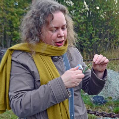 Naturtroende Katariina Krabbe tänder en enriskvist för rena naturen.