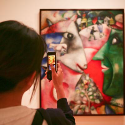 Kvinna tar ett foto med sin telefon på ett museum.