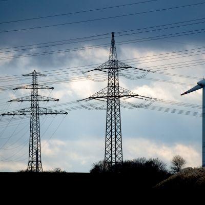 Suurjännitelinjan pylväitä ja tuuliturbiini Saksassa lähellä Hannoveria.