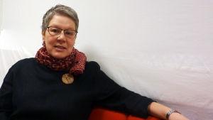 Camilla Grundström sitter i en soffa.