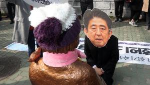 En man iförd en mask, som föreställer Japans premiärminister Shinzo Abe, knäböjer framför statyn i Busan 4.1.2017