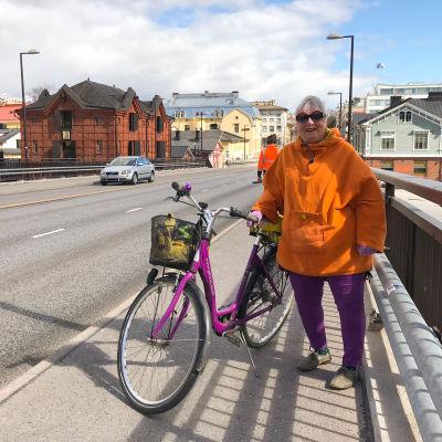 En kvinna med sin cykel på Mannerheimgatans bro.