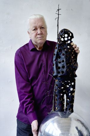 "Pekka Kauhanen tillsammans med en miniatyrversion av skulpturen ""Valon tuoja""."