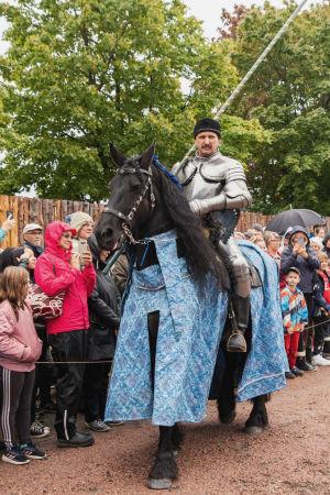 Haarniskaan pukeutunut mies ratsastaa mustalla hevosella, jolla on sininen kirjailtu loimi. Taustalla yleisöä.
