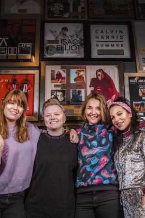 Vilma Alina, Minna Koivisto, Iisa ja Julia Rautio seisovat hymyillen kultalevypeitteisen seinän edessä.