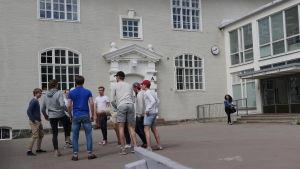 Ungdomar sparkar boll på skolgård
