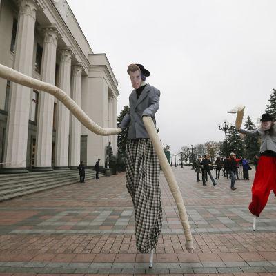 Aktivister på styltor och med långa armar protesterar mot korrupta parlamentariker utanför parlamentet i Kiev i oktober 2014