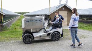 En man håller i ett barn som sitter på en fodertruck. En kvinna närmar sig trucken. I bakgrunden syns skugghus som hör till en rävfarm.