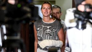 Petra Kvitova vandrar mellan kameror på en presskonferens.