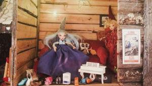 Två dockor och småprylar i ett litet hus byggt av torrfureliknande material.