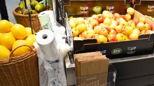 Bild av en låda äpplen i en matbutik. Bredvid finns rullar med plastpåsar, biologiskt nedbrytbara påsar samt en låda med bruna papperspåsar.