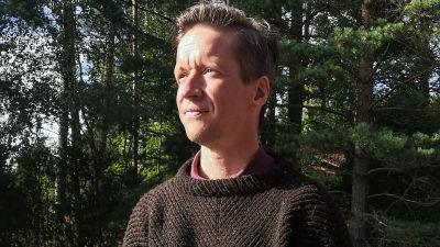 Markus har en brun stickad tröja på sig. Han sitter ute med granar i bakgrunden.