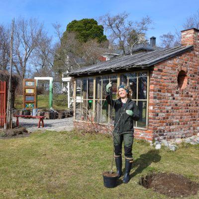 Grönklädd kvinna granskar ett litet äppelträd i en trädgård