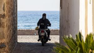 Unga man på moped i Petra på Lesbos i Grekland.