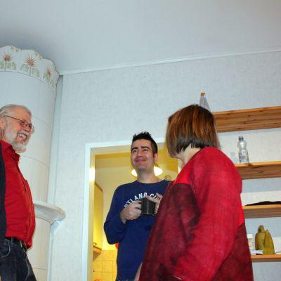 Neljä ihmistä seisoo huoneessa.