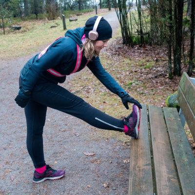 Liisa-Maija Huttunen i träningskläder och reflexsele. Hon står och stretchar benet mot en bänk i en skog.
