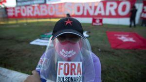 En demonstarnt protesterar mot regeringen och president Bolsonaro utanför Högsta domstolen 9.6.2020 utanför