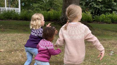 Kolme lapsia juoksevat nurmikolla, strömsövillapaitoja lastenmalleina päälle