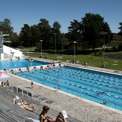Kuvassa on yleiskuvaa Uimastadionilta, missä ihmiset ottavat aurinkoa ja uivat.