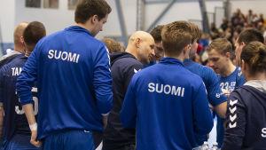 Ola Lindgren instruerar finländska spelare omkring honom.