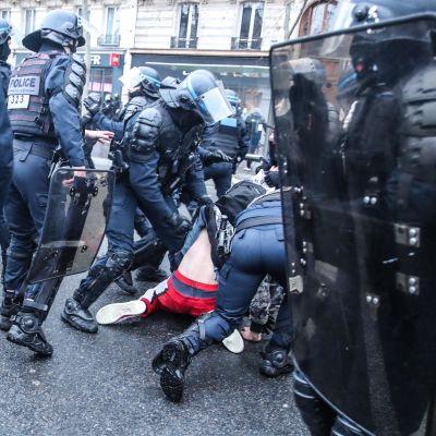 Polis samlade runt en demonstrant i Paris som ligger på marken.