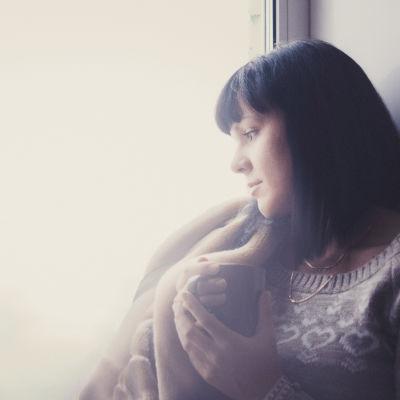Ung flicka i profil framför fönster
