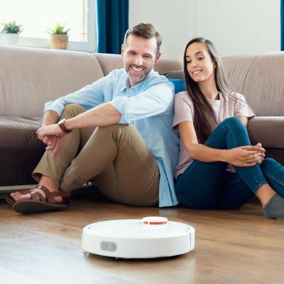 Man och kvinna sitter på golvet och tittar lyckligt på en robotdammsugare