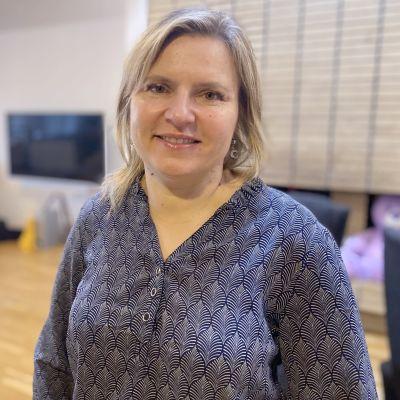 Yrittäjä Riikka-Maria Lemminki seisoo kotonaan olohuoneessa ja katsoo kameraan.