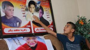 Gazalaispoika näyttää Israelin iskussa kuolleiden veljiensä kuvia.