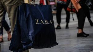 Man med en papperskasse från klädbutiken Zara.