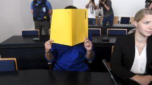 Den yngre brodern täcker sitt ansikte när häktningsförhandlingarna började.