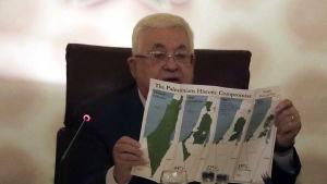 Palestiniernas president Mahmoud Abbas håller upp kartor över Palestina under årens lopp. 1.2.2020