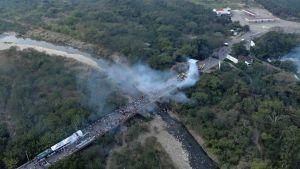 Flygbilder visar rök som stiger från gränsområdet mellan Venezuela och Colombia, där hjälpkonvojer fastnar.