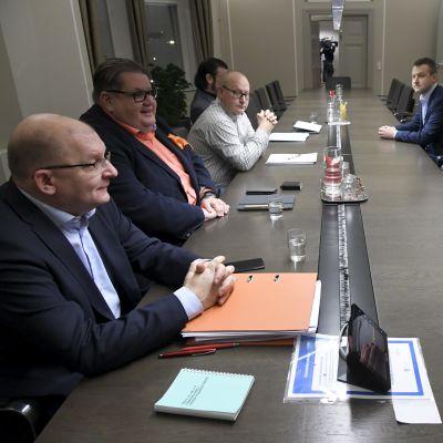 Personer sitter runt ett mötesbord.