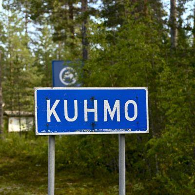 """En trafikskylt med texten """"Kuhmo"""" och skog i bakgrunden."""