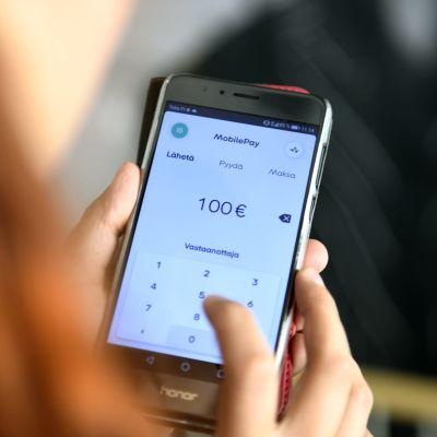 Kännykän näytöllä näkyy Mobilepay sovellus.
