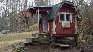 Ett rött hus med vita knutar  i storlek av lekstuga gjord för fåglar. Här finns också talgbollar och fröautomat för fåglar.