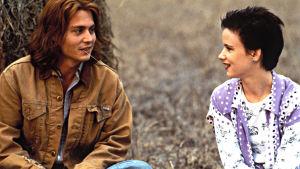 Mies ja nainen istuvat maassa ja katsovat toisiaan. Miehellä on ruoho suussa.